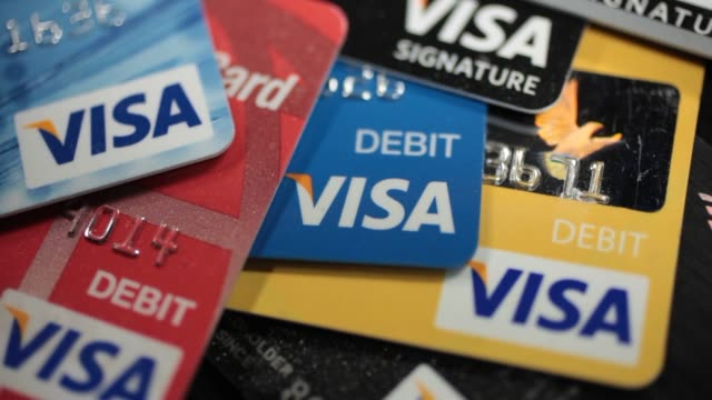 studio broll of various kinds of visa credit cards and debit cards laid out on a black background, studio broll of various kinds of visa credit cards... - credit card stock videos & royalty-free footage