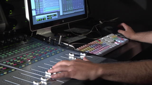 MS Studio engineer actively mixing audio on computer and sound board / New York City, New York, USA
