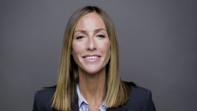 studio headshot of a smiling businesswoman looking at camera - gray background stock videos & royalty-free footage