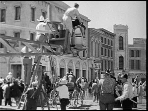 VS Camera crane on Western movie filming stage coach racing down city street cameraman on crane boom operator many extras in street