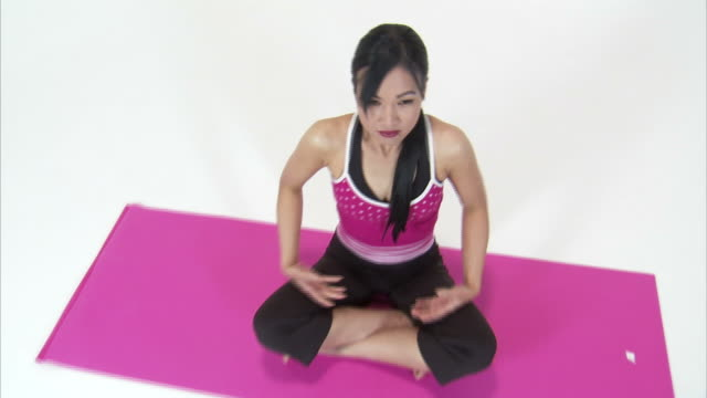 ws cs cu studio portrait of asian woman in lotus position on pink yoga mat / orem, utah, usa - lotus position stock videos & royalty-free footage