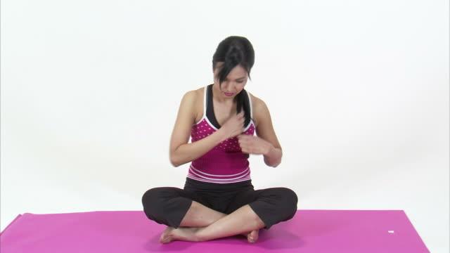 ws studio portrait of asian woman in lotus position on pink yoga mat / orem, utah, usa - lotus position stock videos & royalty-free footage