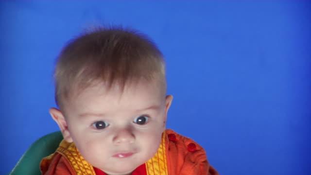 cu studio portrait of baby boy sucking thumb on blue screen - kelly mason videos stock videos & royalty-free footage