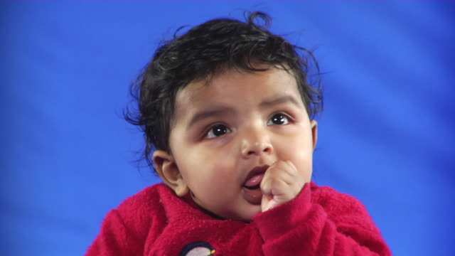 cu studio portrait of baby boy (6-11 months) sucking thumb on blue screen - kelly mason videos stock videos & royalty-free footage