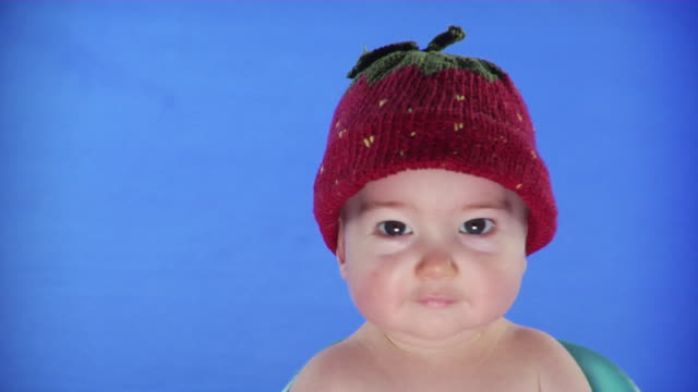 cu studio portrait of baby boy wearing strawberry hat on blue screen - kelly mason videos stock-videos und b-roll-filmmaterial