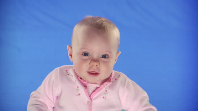 CU Studio portrait of baby girl (6-11 months) on blue screen