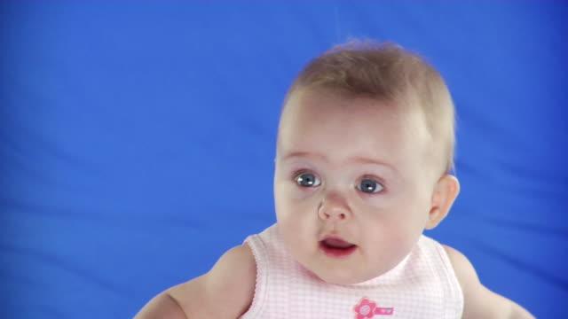 cu studio portrait of baby girl (6-11 months) on blue screen - kelly mason videos stock videos & royalty-free footage