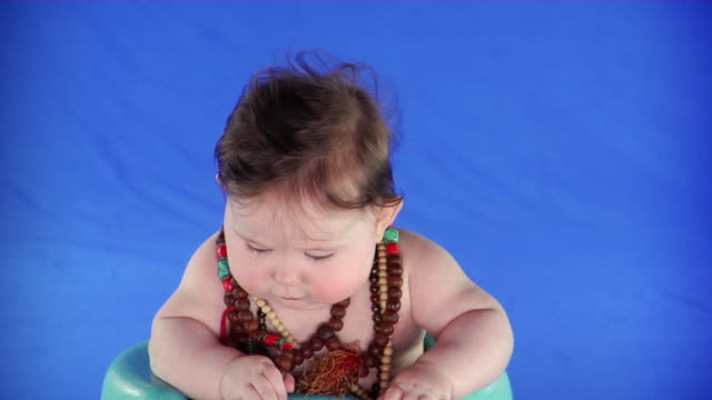ms studio portrait of baby girl (6-11 months) wearing mala beads on blue screen - kelly mason videos stock-videos und b-roll-filmmaterial