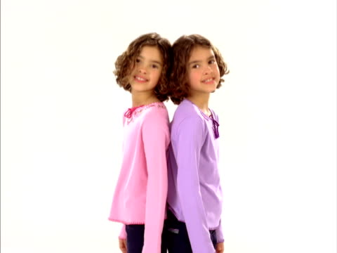 ms, studio portrait of identical twin sisters (8-9) standing back to back, raleigh, north carolina, usa - identical twin stock videos & royalty-free footage