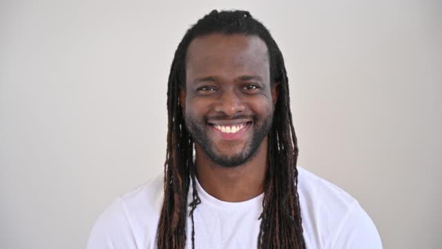 長い三つ編みを持つ中期成人黒人男性のスタジオ肖像画 - ため息点の映像素材/bロール