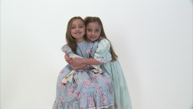 MS Studio portrait of smiling twin sisters (8-9) wearing dresses, hugging / Orem, Utah, USA