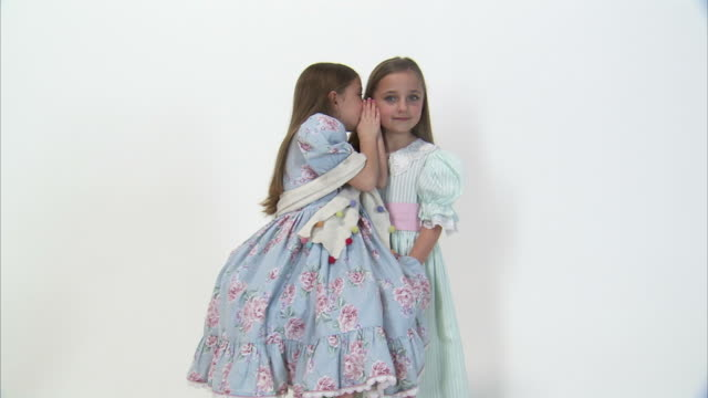 MS Studio portrait of smiling twin sisters (8-9) wearing dresses, whispering in each other's ears / Orem, Utah, USA