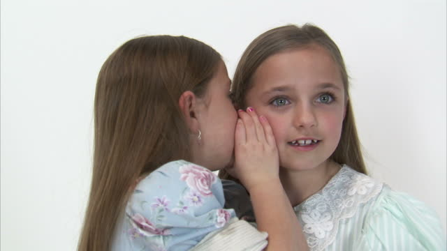 CU Studio portrait of smiling twin sisters (8-9) whispering in each other's ears / Orem, Utah, USA
