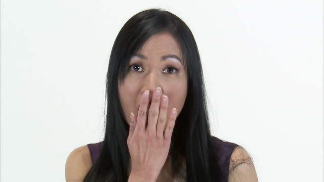 cu studio portrait of surprised asian woman covering mouth with hands / orem, utah, usa - hands covering mouth stock videos and b-roll footage