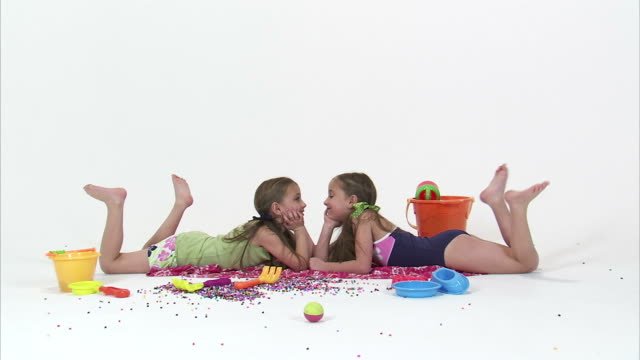WS Studio portrait of twin sisters (8-9) wearing swimwear surrounded with beach toys / Orem, Utah, USA