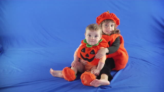 ws studio portrait of two girls (6-11 months, 4-5) wearing pumpkin outfits on blue screen - kelly mason videos stock videos & royalty-free footage