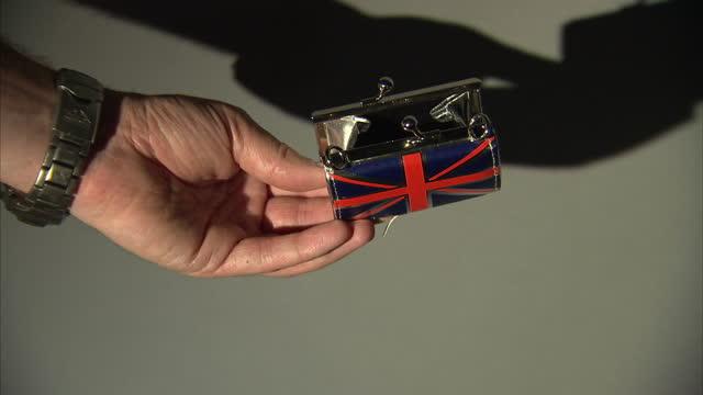 vídeos de stock e filmes b-roll de studio set ups shots british currency pennies and union jack purse on august 05, 2016 in london, england. - european union coin