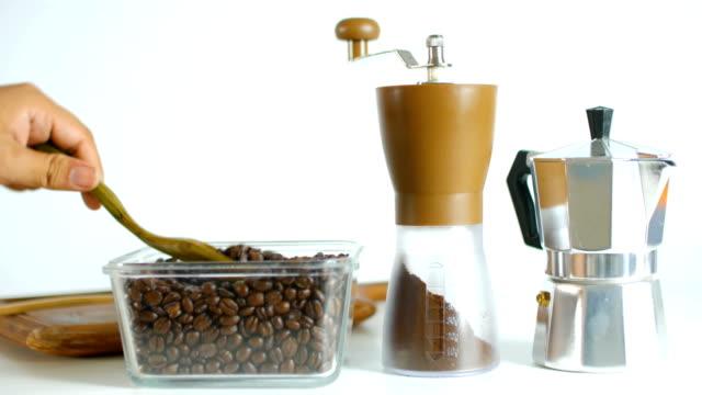 Studioaufnahme: Füllen Kaffeebohnen in manuellen Kaffeemühle auf weißem Hintergrund. Dolly erschossen