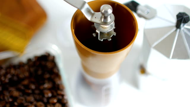 Studio Shot : Filling Coffee Beans into Manual Coffee Grinder on White Background