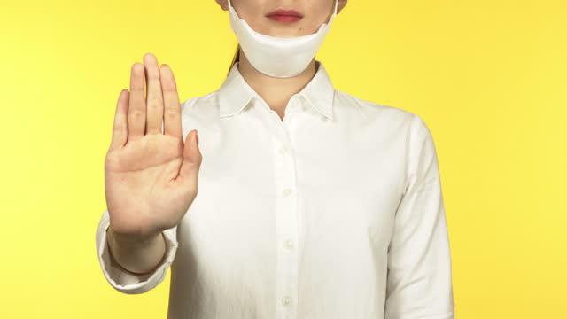 studio shot - hand making refusing sign in front of yellow background / south korea - 断る点の映像素材/bロール