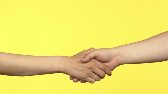 vídeos de stock, filmes e b-roll de studio shot - hands shaking in front of yellow background / south korea - sacudindo