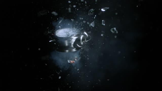 slo mo ws studio shot of alarm clock exploding against black background - 爆発物点の映像素材/bロール