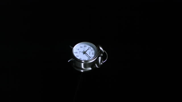 SLO MO WS Studio shot of alarm clock exploding against black background