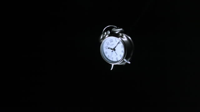 SLO MO WS Studio shot of alarm clock exploding against black background