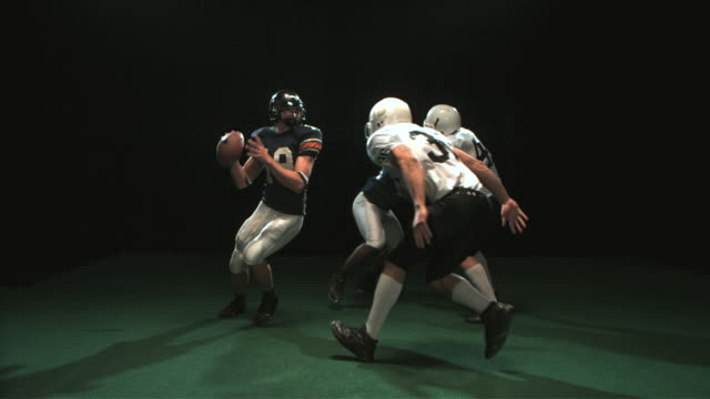 SLO MO WS Studio shot of American football players in action