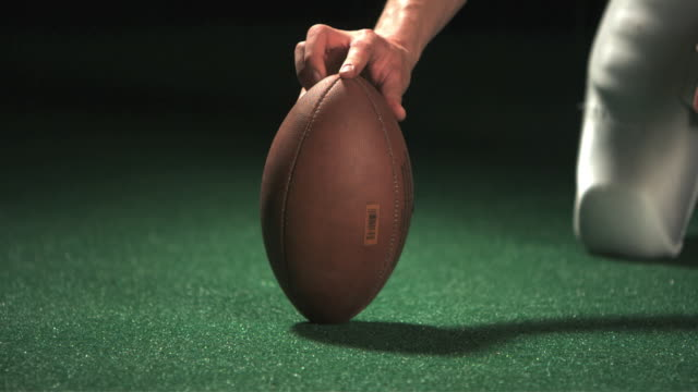 SLO MO CU Studio shot of American football positioned on ground then kicked