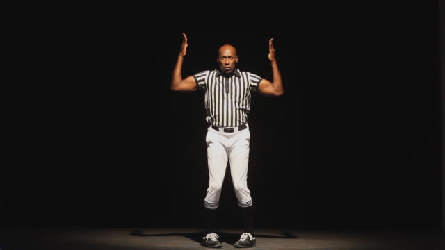 WS Studio shot of American football referee signaling touchdown and dancing