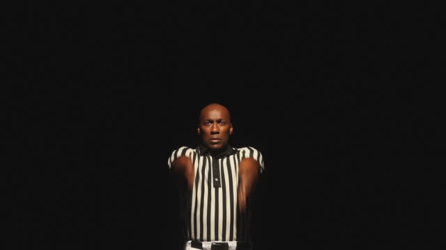 MS Studio shot of American football referee signaling touchdown and dancing