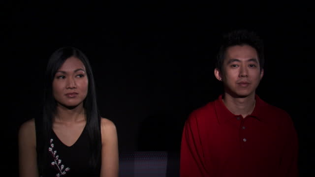 ms studio shot of asian couple sitting side by side and kissing / orem, utah, usa - side by side stock videos & royalty-free footage