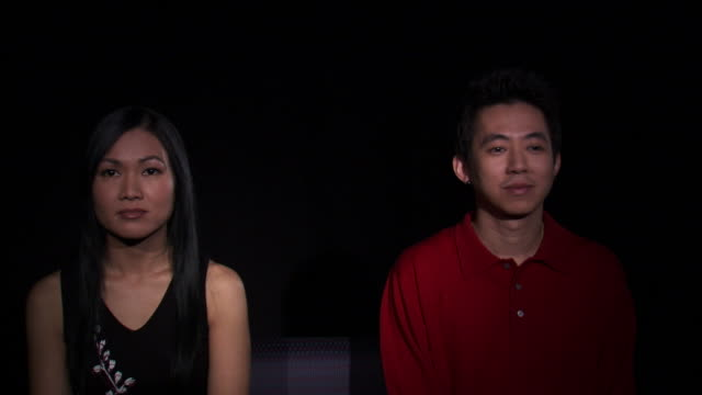 vídeos de stock, filmes e b-roll de ms studio shot of asian couple sitting side by side and kissing / orem, utah, usa - camisa pólo