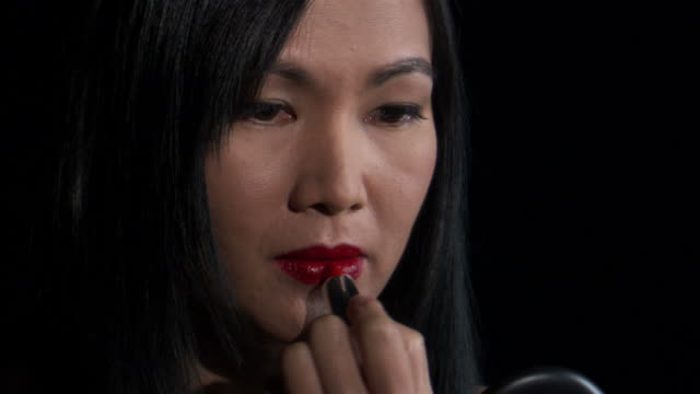 CU Studio shot of Asian woman applying lipstick / Orem, Utah, USA