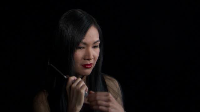 cu studio shot of asian woman combing hair / orem, utah, usa - ノースリーブトップ点の映像素材/bロール
