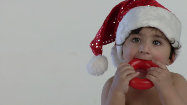 cu, studio shot of baby boy (12-17 months) in santa hat biting teething ring, india - 12 17 months stock videos & royalty-free footage