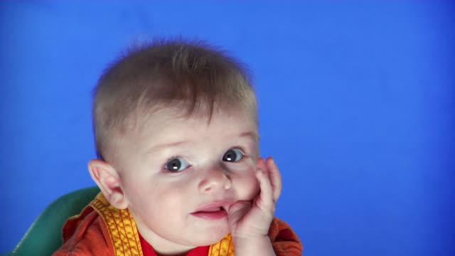 cu studio shot of baby boy on blue screen sucking thumb - kelly mason videos stock videos & royalty-free footage