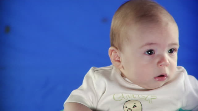 cu studio shot of baby boy (2-5 months) on blue screen - kelly mason videos stock-videos und b-roll-filmmaterial