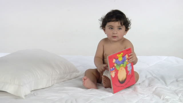 vidéos et rushes de ws, studio shot of baby boy (12-17 months) playing with book, india - 12 17 mois