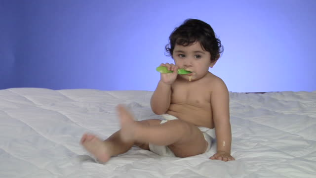 WS, Studio shot of baby boy (12-17 months) playing with plastic spoon, India
