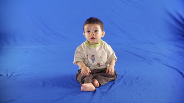WS Studio shot of baby boy (6-11 months) sitting on blue screen