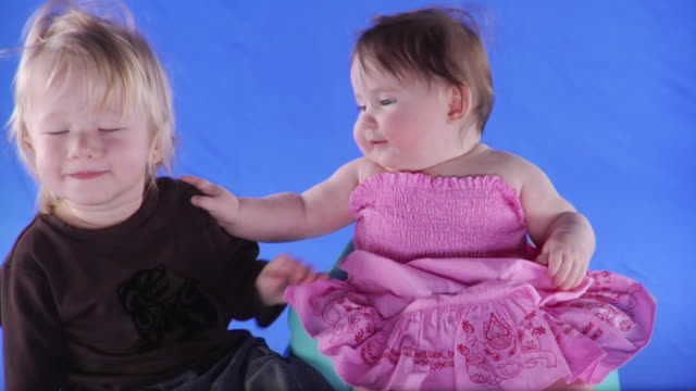 ms studio shot of baby girl (6-11 months) and baby boy (12-17 months) on blue screen - 6 11 months stock videos & royalty-free footage
