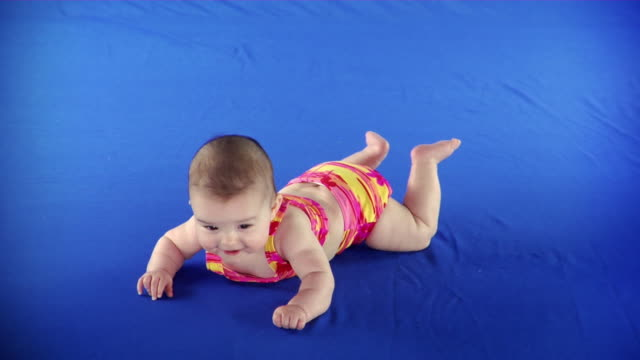 ws studio shot of baby girl (2-5 months) in bathing suit lying on front on blue screen - kelly mason videos stock videos & royalty-free footage