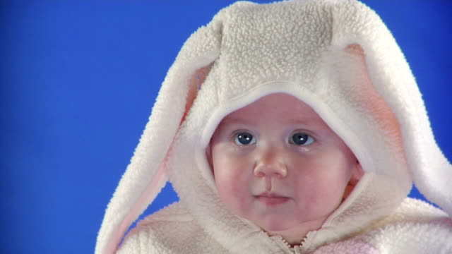 cu studio shot of baby girl (6-11 months) in bunny costume on blue screen - kelly mason videos stock videos & royalty-free footage