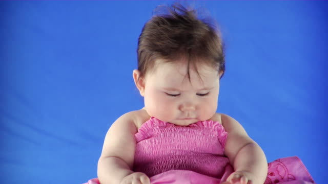 CU Studio shot of baby girl (6-11 months) in pink dress on blue screen