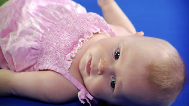 CU Studio shot of baby girl (2-5 months) lying on back on blue screen