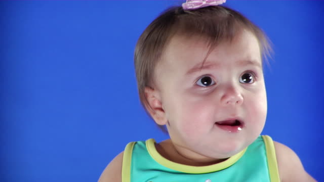 cu studio shot of baby girl (2-5 months) on blue screen - kelly mason videos stock-videos und b-roll-filmmaterial
