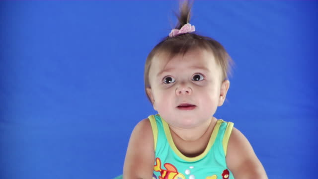 cu studio shot of baby girl (2-5 months) on blue screen - kelly mason videos stock videos & royalty-free footage