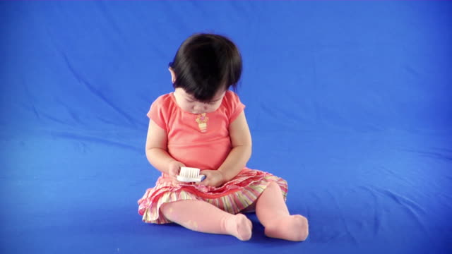 ws studio shot of baby girl (12-17 months) on blue screen - kelly mason videos stock-videos und b-roll-filmmaterial